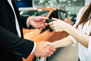 Car salesman handing woman car keys.
