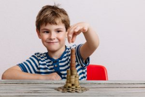 Boy building a stack of money